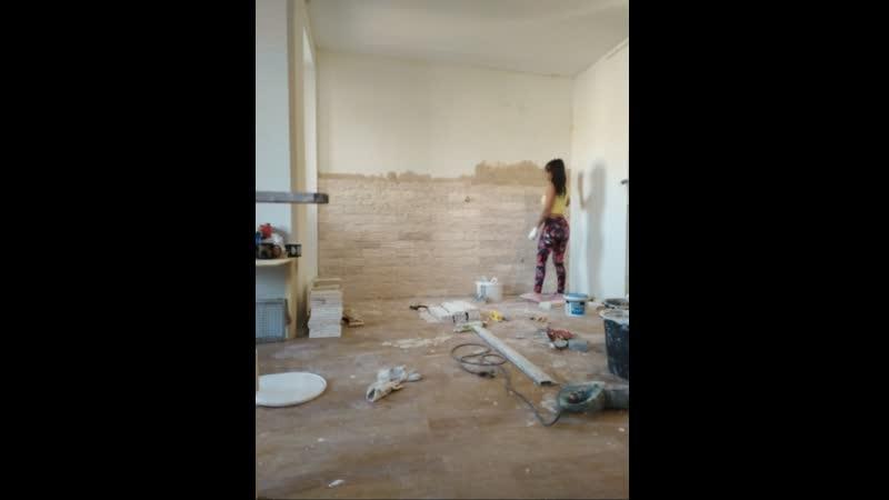 Жена отделывает стену декоративной плиткой под песчанник. Рабочий день в одной минуте
