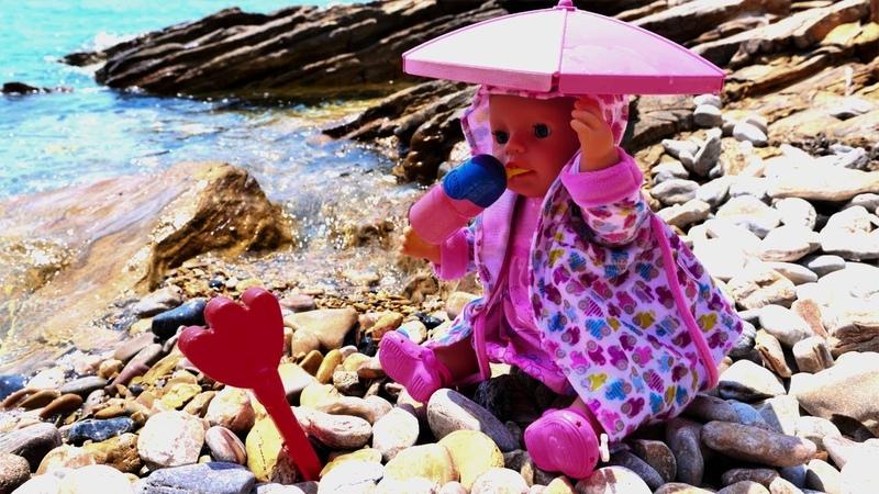 Oyuncak bebek Baby Born denize öğle saatinde gelip gölgeye geçiyor. Bebek bakma oyunu